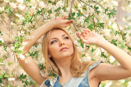 portrait of beautiful woman in blooming tree in spring photo