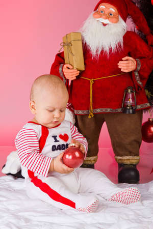 little baby boy with christmas tree and santa playing photo