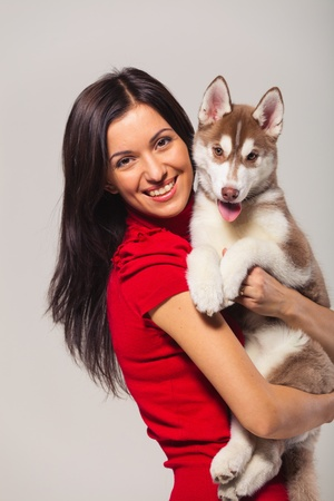 young woman with siberian husky puppy Stock Photo