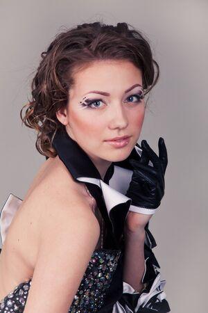 beautiful woman in creative dress on grey background photo