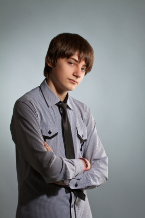 cool boy: portrait of handsome guy in shirt and tie on gray background