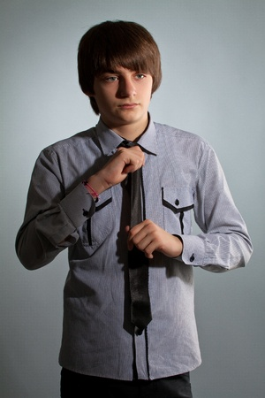 portrait of handsome guy in shirt and tie on gray background photo