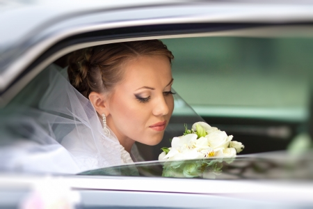 closeup portrait of a pretty bride in a car window photo