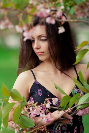 portrait of young beautiful woman in sakura tree