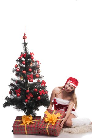 Young happy woman near a Christmas tree. Isolated over white background photo
