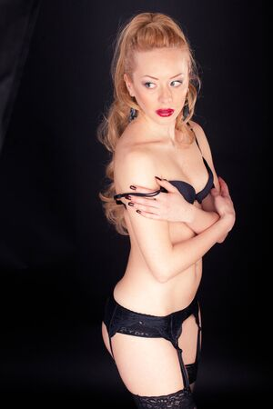 Young sexy woman in lingerie on black background photo
