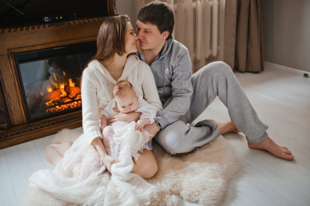 young happy family sitting on floor near fireplace in their apartment photo