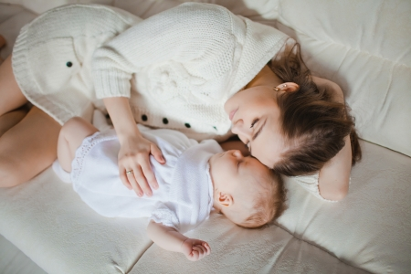 Young caucasian mother taking care of her baby lying on the sofa Stock Photo - 17412734
