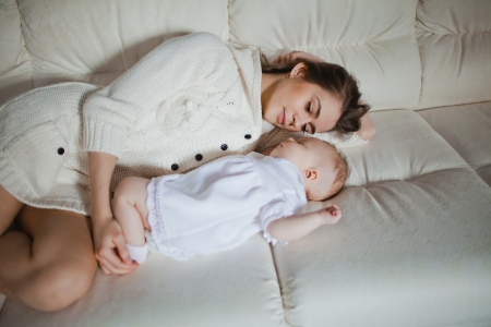 Young caucasian mother taking care of her baby lying on the sofa photo