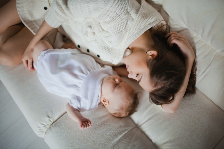 madre y bebe: Joven madre caucásica cuidando a su bebé acostado en el sofá Foto de archivo