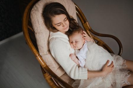 肘掛け椅子に座っている彼女の生まれたばかりの赤ちゃんを保持している若い母親 写真素材