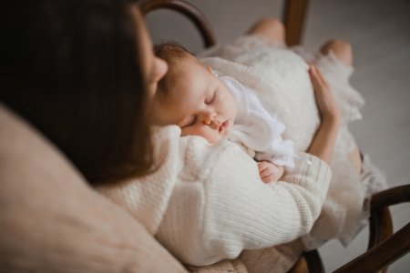 young mother holding her newborn baby sitting in armchair Stock Photo - 17412722