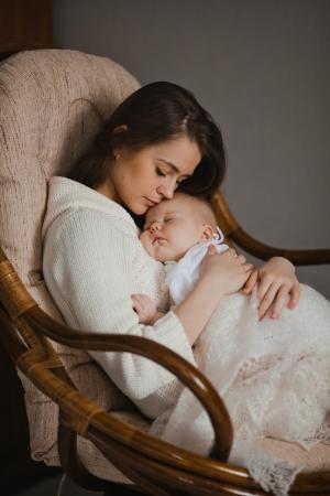 madre y bebe: joven madre sostiene a su bebé recién nacido que se sienta en el sillón