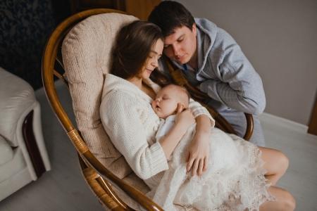 若い母親と父親は彼らのアパートで彼女の生まれたばかりの赤ちゃんを保持