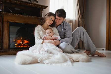 young happy family sitting on floor near fireplace in their apartment