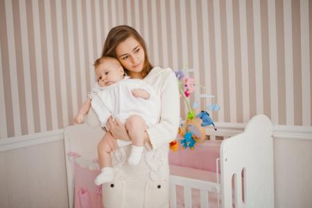若い白人の母彼女の赤ちゃんの世話をして 写真素材