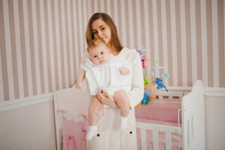 Young caucasian mother taking care of her baby photo