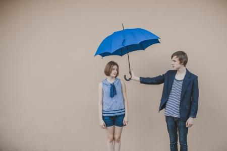 傘を持って幸せな若いカップル 写真素材