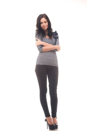 Full length of a smiling young female model standing over white background photo