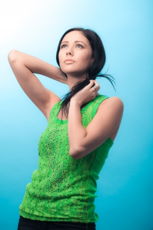 Beautiful casual young woman standing against blue background photo