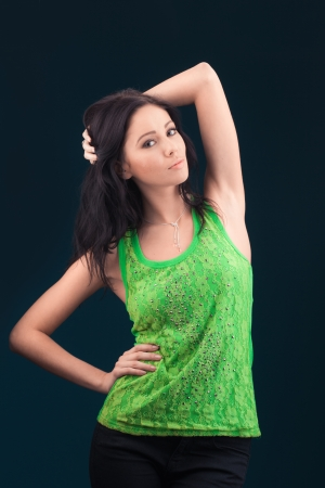 Beautiful casual young woman standing against dark background photo