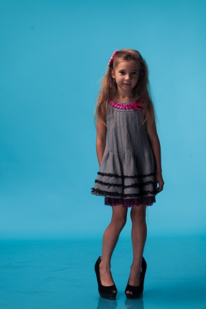 little girl wearing big mothers shoes on blue background photo