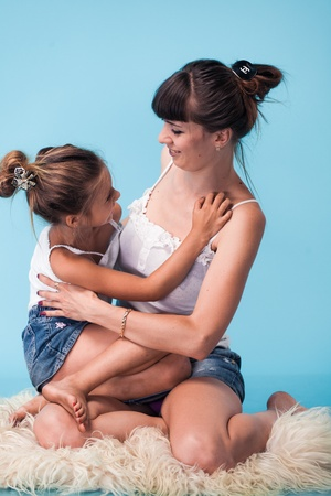 Young mother with daughter on blue background photo
