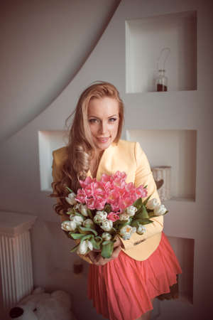 beautiful woman with tulips indoor Stock Photo - 18493388