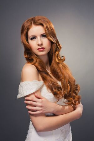 beautiful bride with curly red hair in wedding dress photo