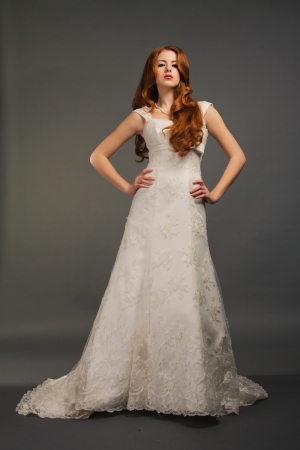 beautiful bride with curly red hair in luxury wedding dress with tail photo