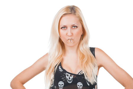 inflating: Fashion rock woman model in skull t-shirt inflating bubble gum isolated on white background