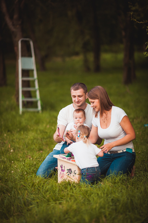 Happy family with nesting box and colorful paints in green summer forest photo