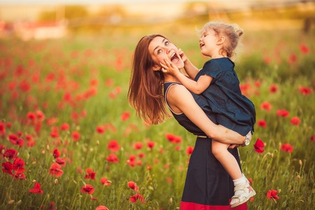 Young beautiful mother with daughter in the poppy meadow photo