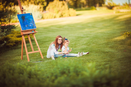 Mother and little daughter paint together in a park photo