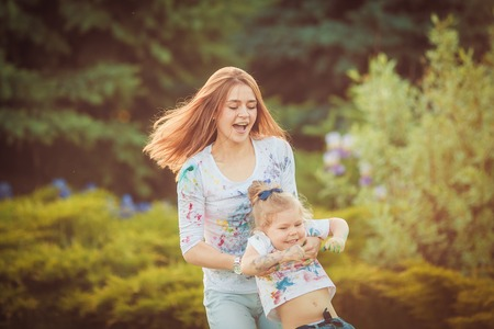 Mother and little daughter playing together in a park photo