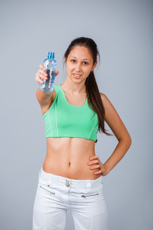 gulp: Sporty Female holding in hand sparkling mineral bottle of water isolated on background