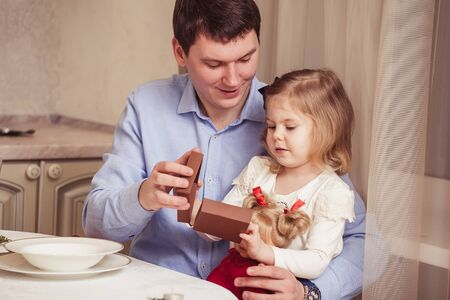 25 30 years: Happy father and cute little daughter at the festive holiday table