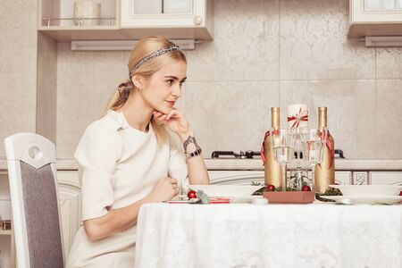 Beautiful young blond woman at festive table photo