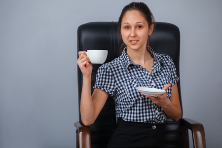 Business woman sitting on a chair with cup of tea. Stock Photo