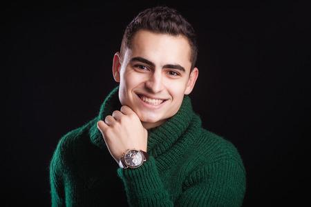 chronograph: Retrato del hombre atractivo en el su�ter verde sobre fondo oscuro que llevaba un reloj de pulsera cron�grafo