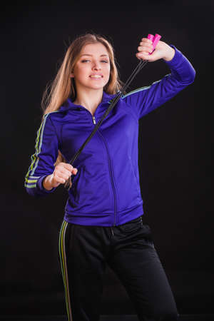 jogger: Fitness woman studio shot with jogger jumping rope