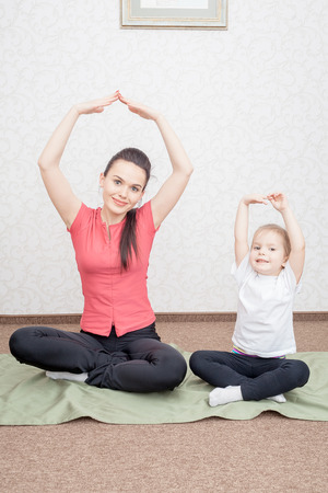 karemat: Mother and daughter practicing yoga at home