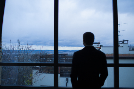 business suit: Businessman thinking in office, looking out of windows to downtown