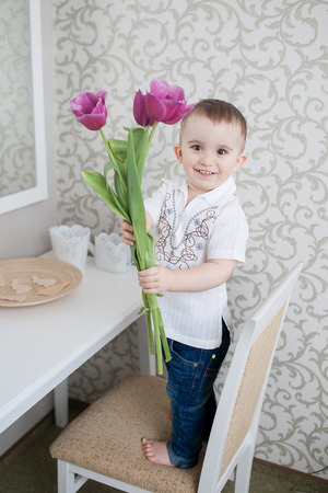 Cute baby boy with tulip flowers indoor portrait photo
