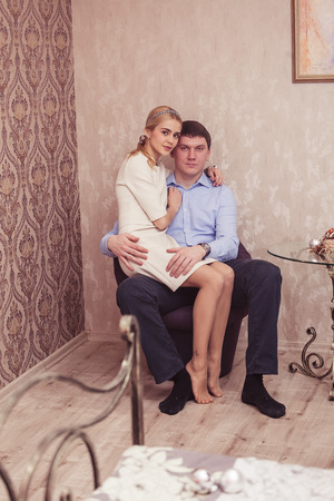 25 to 30 years old: Cheerful young couple sitting indoor