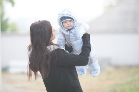 Young mother holding baby outdoor in autumn