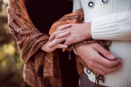 hug: closeup hands of happy young couple in love outdoor in autumn