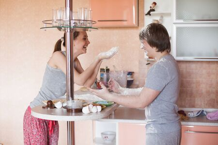 20 24 years: young happy couple cooking together in kitchen