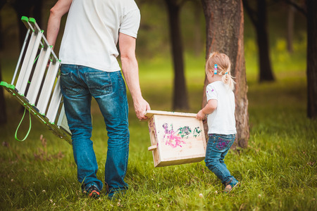 making fun: Happy father making Wooden birdhouse with daughter in summer green park Stock Photo