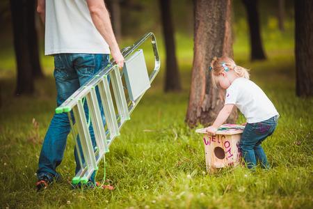 幸せな父の夏緑の公園で娘と木製の巣箱を作る